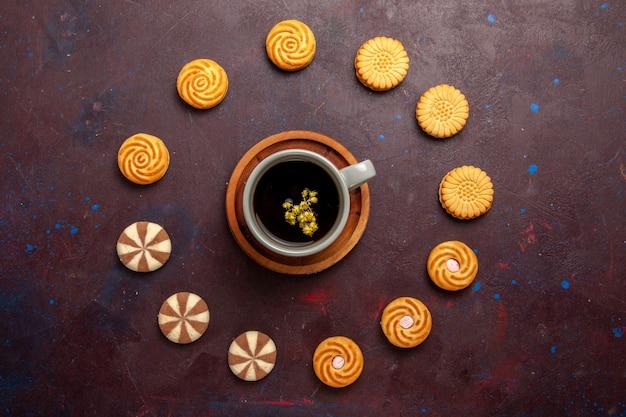 Draufsicht tasse kaffee mit verschiedenen keksen auf dunklem hintergrund kekskekszuckerkuchen