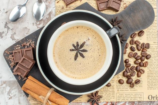 Draufsicht tasse kaffee schokolade zimtstangen auf holzbrett geröstete kaffeebohnen anis löffel auf tisch