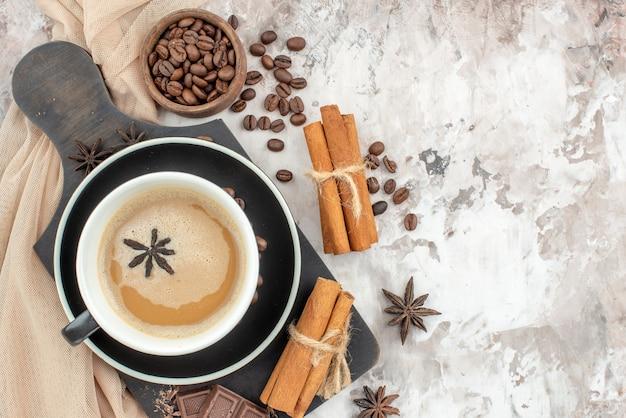 Draufsicht tasse kaffee schokolade zimtstangen auf holzbrett geröstete kaffeebohnen in holzschale anis auf tisch frei platz