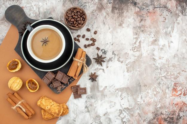 Draufsicht tasse kaffee schokolade zimtstangen kekse auf holzbrett geröstete kaffeebohnen in holzschale auf tisch mit kopierplatz