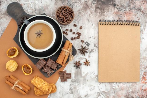 Draufsicht tasse kaffee schokolade zimtstangen kekse auf holzbrett geröstete kaffeebohnen in holzschale notizbuch auf tisch