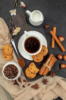 Draufsicht tasse kaffee stern anis kekse löffel auf holzbrett kaffeebohnen in schüssel milchschale auf dunkler oberfläche