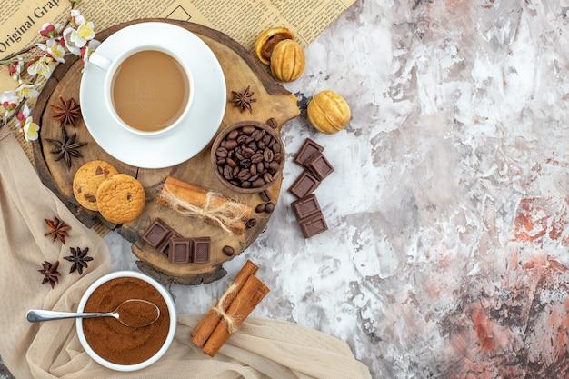 Draufsicht tasse kaffeekekse schüssel mit gerösteten kaffeebohnen schokolade zimtstangen anis auf holzbrett kakaoschale auf tischkopierplatz
