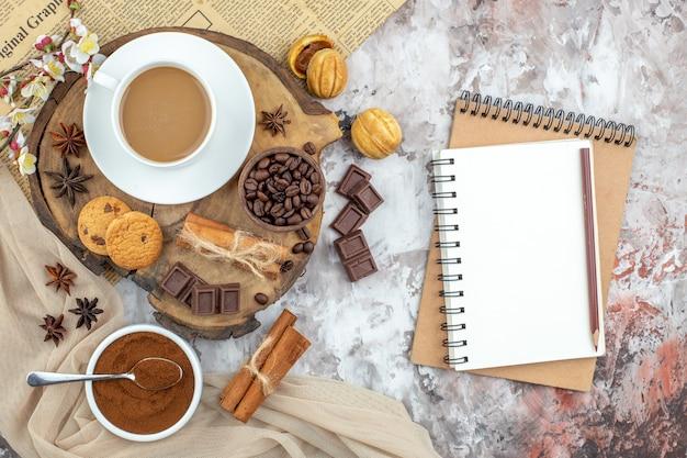 Draufsicht tasse kaffeekekse schüssel mit gerösteten kaffeebohnen schokolade zimtstangen anis auf holzbrett kakaoschale notizbücher auf dem tisch