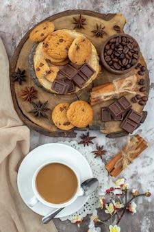 Draufsicht tasse kaffeeschale mit gerösteten kaffeebohnen und kakaoschokolade zimtstangen kekse auf holzbrett auf dem tisch