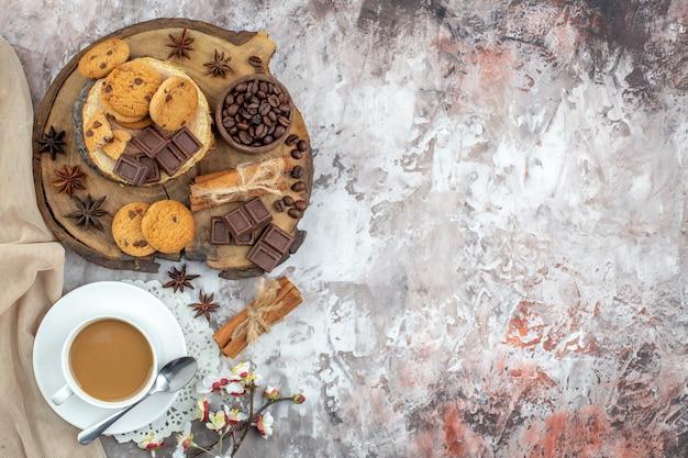 Draufsicht tasse kaffeeschale mit gerösteten kaffeebohnen und kakaoschokolade zimtstangen kekse auf holzbrett auf tisch mit freiem platz