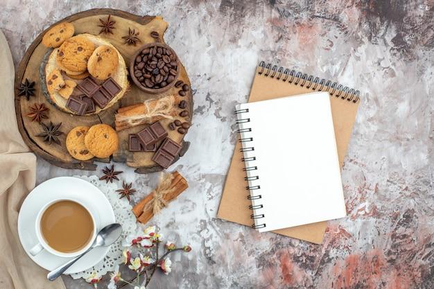 Draufsicht tasse kaffeeschale mit gerösteten kaffeebohnen und kakaoschokolade zimtstangen kekse auf holzbrett notebooks auf dem tisch
