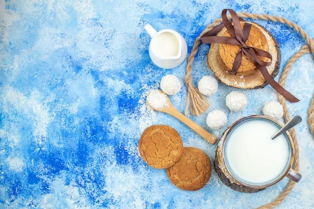 Draufsicht tasse milch auf holzbrett kokoskugeln kokospulver in holzlöffel seil kekse mit band auf blauem weißem hintergrund gebunden