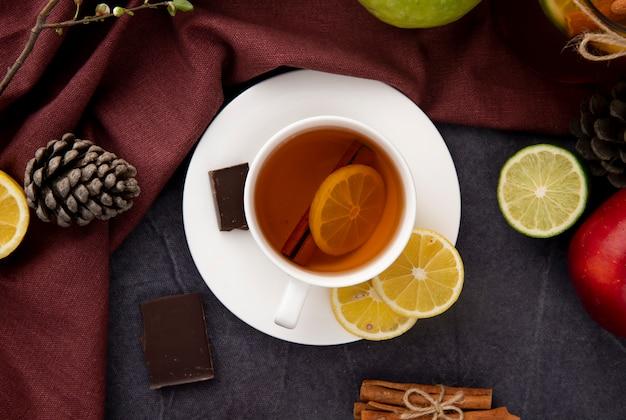 Draufsicht tasse schwarzen tee mit scheibe zitronenzimt dunkle schokolade äpfel tannenzapfen und limettenscheibe