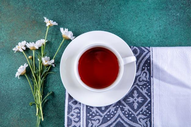Draufsicht tasse tee auf küchentuch mit gänseblümchen auf grün