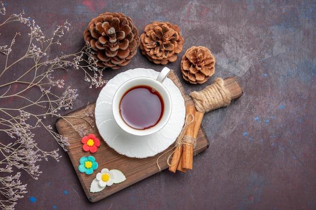 Draufsicht tasse tee in glastasse mit teller auf dunklem raum