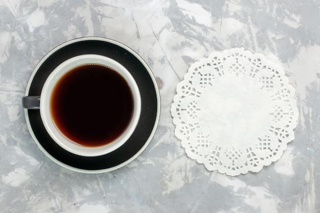 Draufsicht tasse tee in tasse und teller auf der hellweißen oberfläche