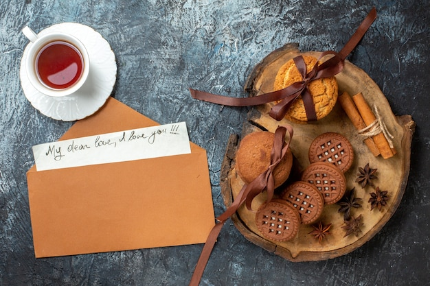 Draufsicht tasse tee kekse auf holzbrett meine liebe liebe ich liebe dich geschrieben auf papierumschlag auf dunklem tisch