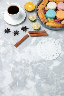 Draufsicht tasse tee mit bagels und macarons auf weißem schreibtisch
