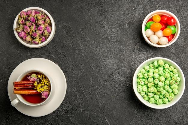 Draufsicht tasse tee mit bonbons auf grauem schreibtisch teefarbe regenbogengeschmack