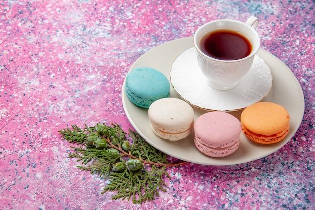 Draufsicht tasse tee mit bunten französischen macarons auf der rosa oberfläche