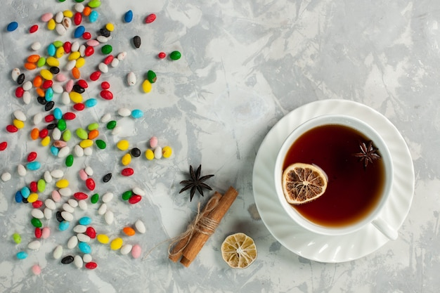 Draufsicht tasse tee mit bunten verschiedenen bonbons auf hellweißer oberfläche