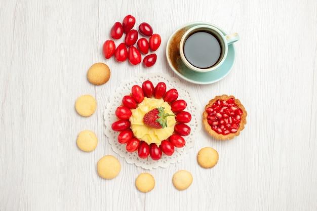 Draufsicht tasse tee mit cremigem kuchen und früchten auf weißem schreibtisch