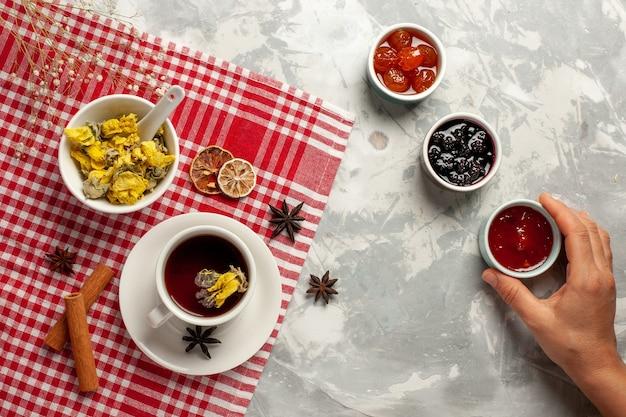 Draufsicht tasse tee mit dessert und verschiedenen marmeladen auf hellweißem backgruond-fruchtmarmeladentee süßem zucker