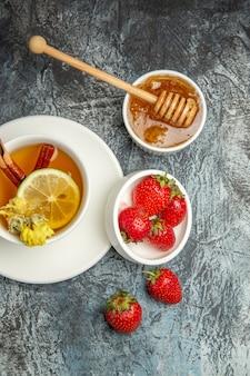 Draufsicht tasse tee mit erdbeeren und honig auf dunkler oberfläche fruchttee beere