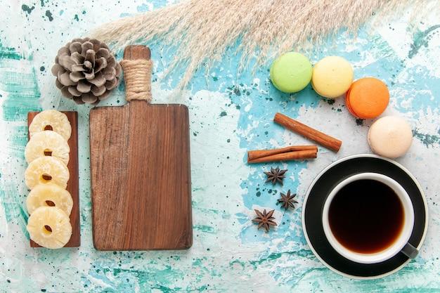 Draufsicht tasse tee mit französischen macarons auf der blauen oberfläche