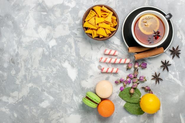 Draufsicht tasse tee mit französischen macarons auf hellweißer oberfläche