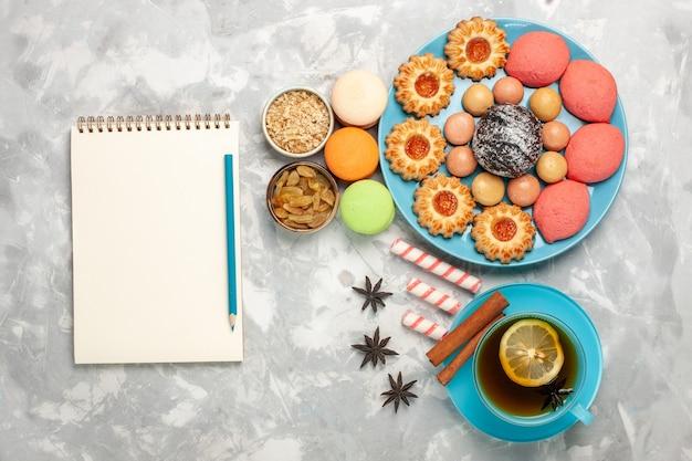 Draufsicht tasse tee mit französischen macarons keksen und kuchen auf weißer oberfläche