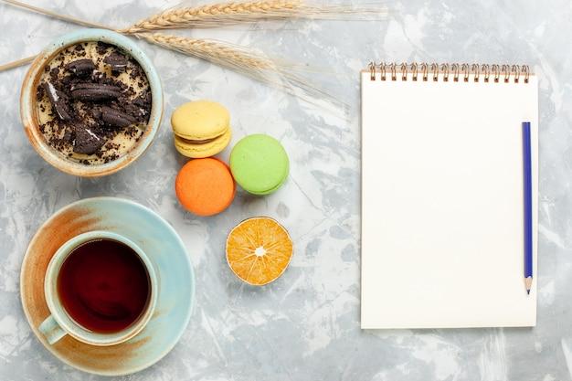 Draufsicht tasse tee mit französischen macarons und schokoladenplätzchen-dessert auf hellweißem schreibtischplätzchen süß backen zuckerkuchenplätzchen