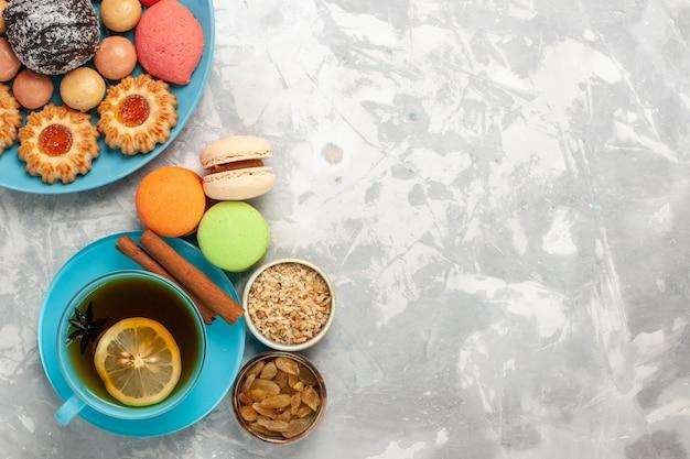 Draufsicht tasse tee mit französischen macarons zuckerkeksen und kuchen auf weißer oberfläche