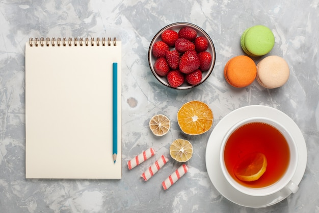 Draufsicht tasse tee mit frischen roten erdbeeren und französischen macarons auf weißem schreibtisch