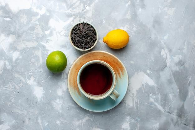 Draufsicht tasse tee mit frischen zitronen und getrocknetem tee auf dem leuchttisch, teefrucht zitrusfarbe