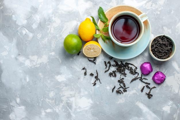 Draufsicht tasse tee mit frischen zitronensüßigkeiten und getrocknetem tee auf weißem tisch, teefruchtzitrusfrüchten