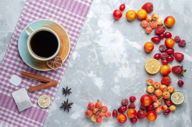 Draufsicht tasse tee mit früchten zimt auf leichtem schreibtisch obstbeere frisches vitamin