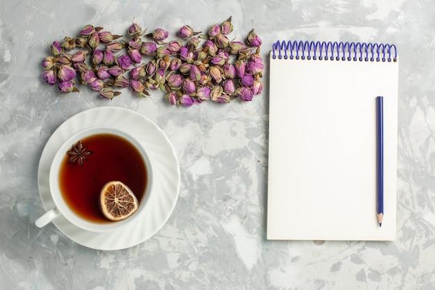 Draufsicht tasse tee mit getrockneten kleinen blumen und notizblock auf dem hellweißen schreibtisch
