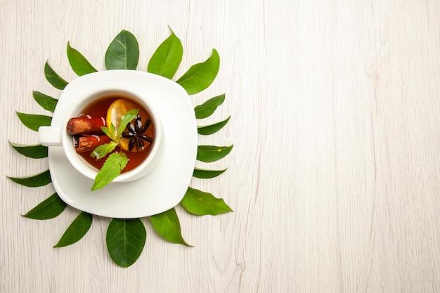Draufsicht tasse tee mit grünen blättern auf weißem schreibtisch farbe tee fruchtzeremonie