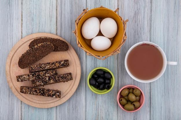 Draufsicht tasse tee mit hühnereiern im korb mit schwarzbrotscheiben auf ständer und oliven auf grauem hintergrund