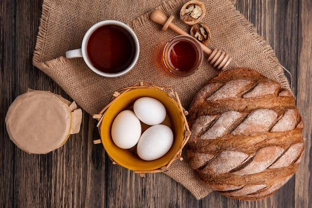 Draufsicht tasse tee mit joghurt hühnereiern honig und schwarzbrot auf einer beigen serviette