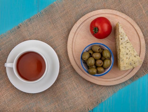Draufsicht tasse tee mit käseoliven und tomaten auf einem ständer auf einer beigen serviette