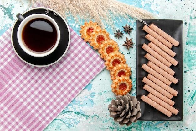 Draufsicht tasse tee mit keksen auf der blauen oberfläche