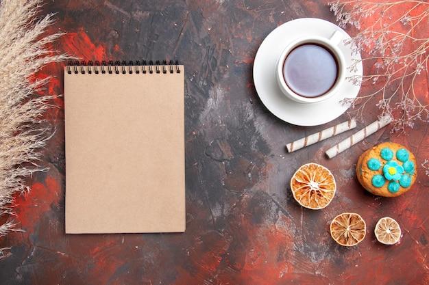 Draufsicht tasse tee mit keksen auf dunklem boden