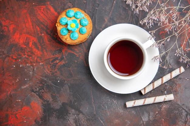 Draufsicht tasse tee mit keksen auf dunklem tisch