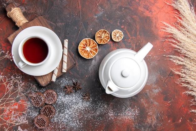 Draufsicht tasse tee mit keksen auf dunkler tischkeks dunkle zeremonie