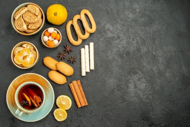 Draufsicht tasse tee mit keksen und früchten auf dunklem tischplätzchenkuchen-kekstee