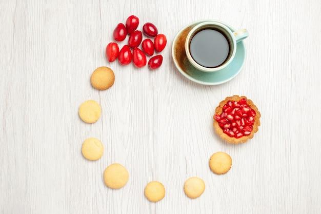 Draufsicht tasse tee mit keksen und früchten auf weißem schreibtisch