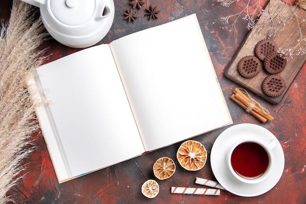 Draufsicht tasse tee mit keksen und heft auf dunklem tisch