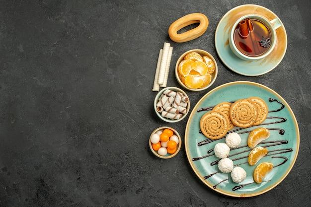 Draufsicht tasse tee mit keksen und mandarinen auf dunklem hintergrund