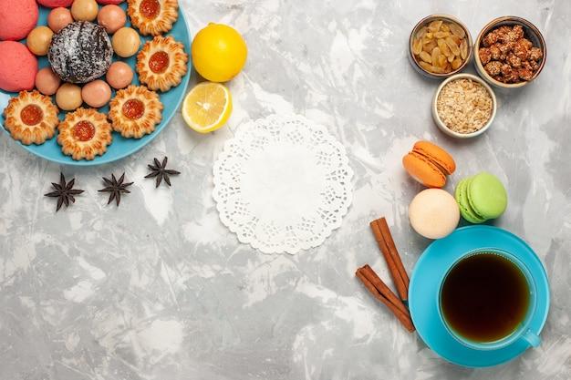Draufsicht tasse tee mit keksen und rosa kuchen auf weißem schreibtisch