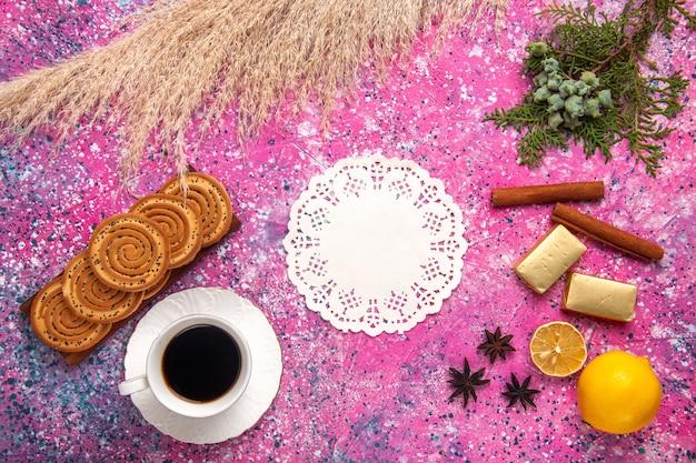 Draufsicht tasse tee mit keksen zitrone und zimt auf hellrosa schreibtisch.