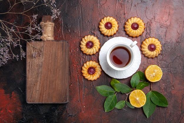 Draufsicht tasse tee mit kleinen keksen auf dem dunklen tischdessertkeks süß