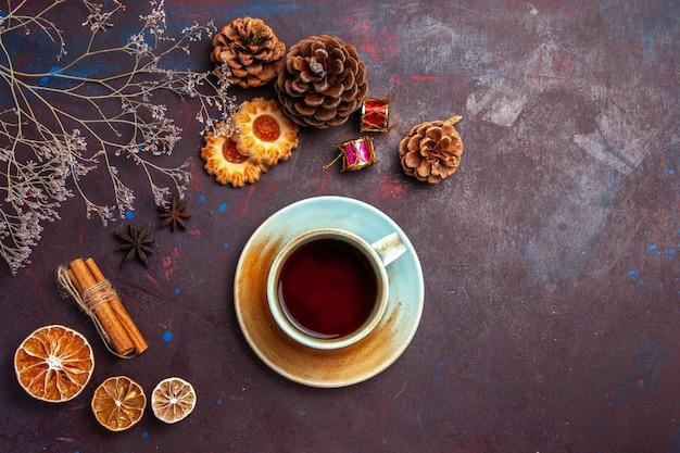 Draufsicht tasse tee mit kleinen keksen auf dunklem hintergrund zuckerkeksplätzchen süß